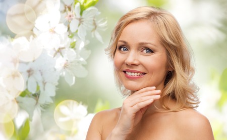 beauty, people and skincare concept - smiling middle aged woman with bare shoulders touching face over green natural background with cherry blossom