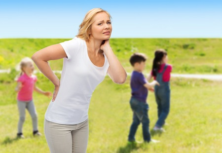 reins: people, healthcare, children and parenthood concept - unhappy woman suffering from pain in back or reins over group of little kids outdoors background