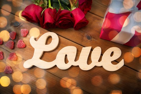 uprzejmości: romance, valentines day and holidays concept - close up of word love, red roses and gift box on wood