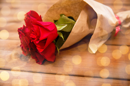 uprzejmości: love, date, flowers, valentines day and holidays concept - close up of red roses bunch wrapped into brown paper on wooden table