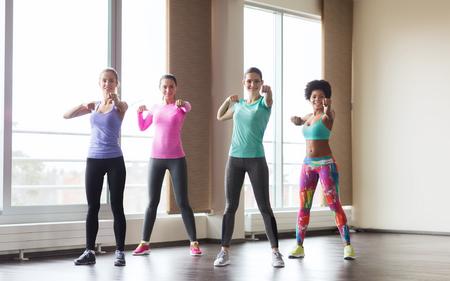 defensa personal: fitness, deporte, entrenamiento, gimnasio y artes marciales concepto - grupo de mujeres felices que se resuelven y lucha en el gimnasio Foto de archivo