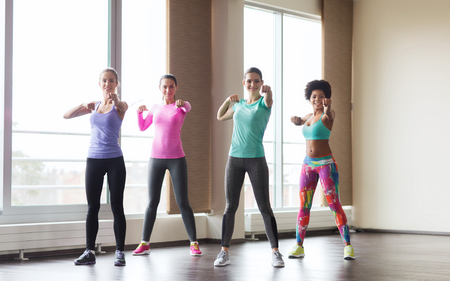fitness, sport, training, gym and martial arts concept - group of happy women working out and fighting in gym Stock Photo