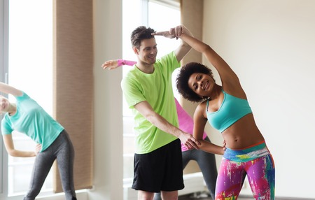 fitness, sport, training, gym and lifestyle concept - group of smiling people stretching in gym Stock Photo