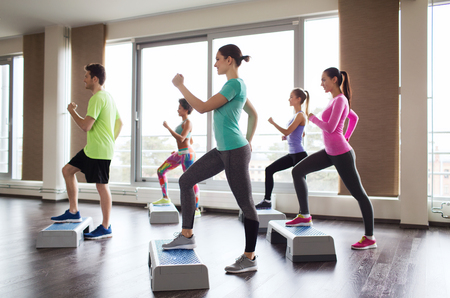 fitness, deporte, entrenamiento, aeróbic y concepto de la gente - grupo de personas que trabajan con motores paso a paso en el gimnasio