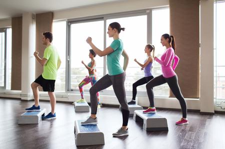 fitness, sport, szkolenia, aerobik i koncepcja ludzie - grupa ludzi pracuje obecnie z steppery w siłowni