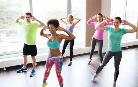 zumba: fitness, deporte, la danza y el estilo de vida concepto - grupo de gente sonriente con zumba baile entrenador en el gimnasio o estudio