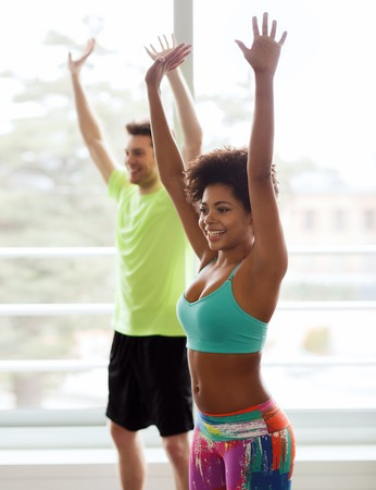 women sport: fitness, sport, dance and lifestyle concept - group of smiling people with coach dancing zumba in gym or studio