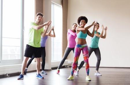 Fitness, Sport, Tanz und Lifestyle-Konzept - Gruppe von lächelnden Menschen mit Trainer Tanz Zumba im Fitness-Studio oder Studio Standard-Bild - 53070501