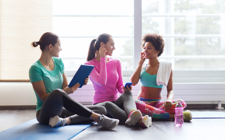 social networking: fitness, sport, technology and lifestyle concept - group of happy women with smartphone, earphones and tablet pc computer listening to music in gym