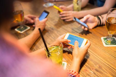 レジャー、技術、ライフ スタイル、人々 の概念 - レストランでメッセージングのスマート フォンと手のクローズ アップ 写真素材