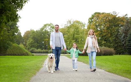 mom dad: familia, mascotas, animales domésticos y las personas concepto - familia feliz con el perro labrador retriever caminando en el parque de verano Foto de archivo