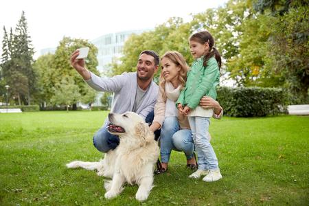 familia, animal doméstico, animal, la tecnología y la gente concepto - familia feliz con el perro labrador retriever teniendo selfie por teléfono inteligente en el parque Foto de archivo