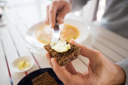 레스토랑, 커플 및 휴가 개념 - 확대 적용하고 빵에 버터를 확산 손을 닫