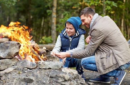 campfire: camping, tourism, hike, family and people concept - happy father and son roasting marshmallow over campfire
