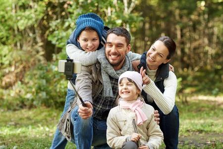 los viajes, el turismo, la caminata, la tecnología y el concepto de la gente - familia feliz que toma el cuadro con el palillo autofoto teléfono inteligente en maderas