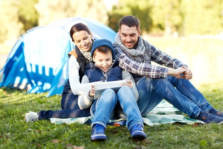 tent: camping, tourism, hike, technology and people concept - happy family with tablet pc computer and tent at camp site Stock Photo