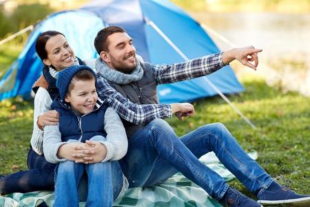 camping, turismo, ir de excursión y la gente concepto - familia feliz en tienda de campaña en camping señalar con el dedo a algo
