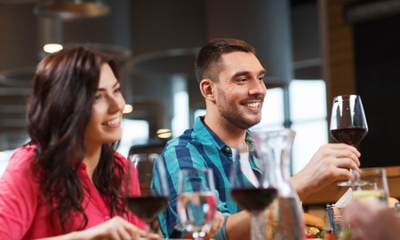leisure, celebration, food and drinks, people and holidays concept - happy couple and friends clinking glasses of wine at restaurant Stock Photo