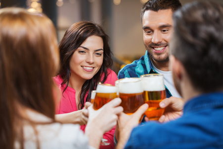 leisure, drinks, celebration, people and holidays concept - smiling friends drinking beer and clinking glasses at restaurant or pub