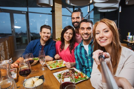 per il tempo libero, la tecnologia, l'amicizia, la gente e le vacanze concetto - amici felici a cena e immagine presa dal bastone selfie al ristorante