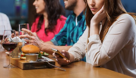 restaurant dining: leisure, technology, internet addiction, lifestyle and people concept - woman with smartphone and friends at restaurant