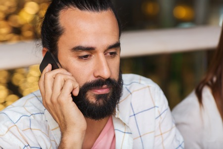 leisure, technology, lifestyle, communication and people concept - sad man calling on smartphone at restaurant Stock Photo