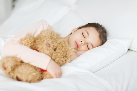wellness sleepy: people, childhood, rest and comfort concept - girl sleeping with teddy bear toy in bed at home Stock Photo