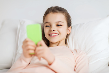 girl: la gente, los niños, el descanso y el concepto de la tecnología - la muchacha sonriente feliz con el teléfono inteligente despierto en la cama en su casa Foto de archivo