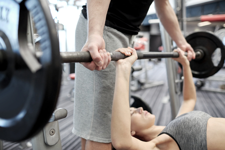 Weights: sport, fitness, teamwork, weightlifting and people concept - close up of young woman and personal trainer with barbell flexing muscles in gym