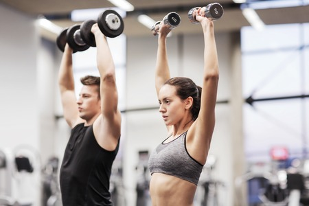 Weights: sport, fitness, lifestyle and people concept - smiling man and woman with dumbbells flexing muscles in gym