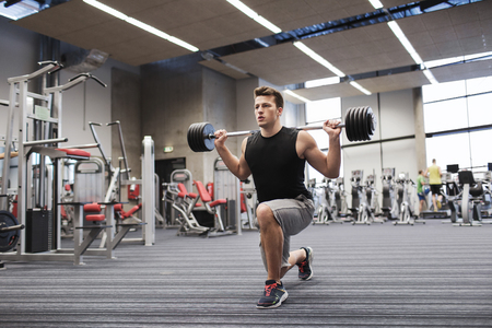 sport, bodybuilding, lifestyle and people concept - young man with barbell flexing muscles and making shoulder press lunge in gym Standard-Bild