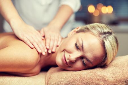 massage: gens, beauté, spa, mode de vie sain et de détente notion - close up de la belle jeune femme allongée, les yeux fermés et ayant massage des mains dans le spa