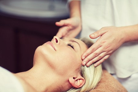 people, beauty, spa, healthy lifestyle and relaxation concept - close up of beautiful young woman lying with closed eyes and having face or head massage in spa Zdjęcie Seryjne