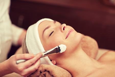 tratamientos corporales: personas, belleza, spa, cosmetología y cuidado de la piel concepto - cerca de la hermosa mujer joven tendido con los ojos cerrados y cosmetóloga que aplican la máscara facial con brocha en el spa