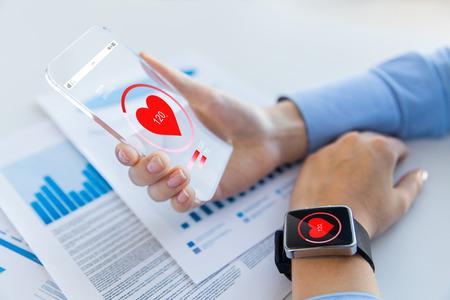 기술, 건강 관리 및 사람들이 개념 - 투명 한 스마트 폰 및 smartwatch 사무실에서 심장 아이콘을 들고 여자 손 가까이