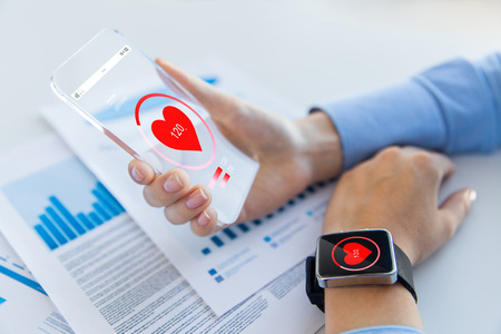 technology, health care and people concept - close up of woman hand holding transparent smartphone and smartwatch with heart icon at office Standard-Bild