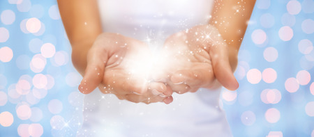twinkles: people and magic concept - close up of twinkles or fairy dust on female cupped hands over blue background with holidays lights Stock Photo