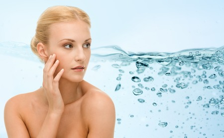 touching face: beauty, people and health concept - young woman with bare shoulders touching her face over water splash on blue background