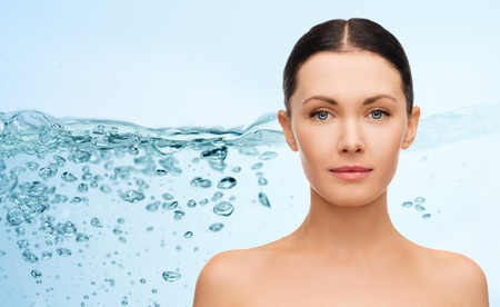 bare shoulders: beauty, people, moisturizing, body care and health concept - young woman face with bare shoulders over water splash background