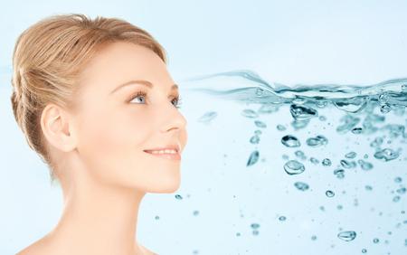 belleza, gente, hidratación, cuidado del cuerpo y el concepto de salud - cara de la mujer joven y sonriente sobre el fondo salpicaduras de agua Foto de archivo