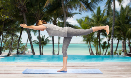 female legs: fitness, sport, people and healthy lifestyle concept - woman making yoga warrior pose on mat over hotel resort pool on tropical beach background