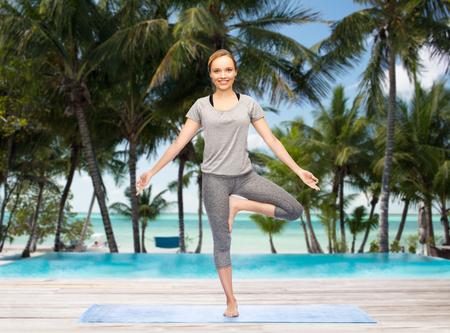 beach mat: fitness, sport, people and healthy lifestyle concept - woman making yoga in tree pose on mat over hotel resort pool on tropical beach background