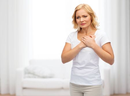 people, healthcare, heart disease and problem concept - unhappy woman suffering from heartache over living room background 版權商用圖片