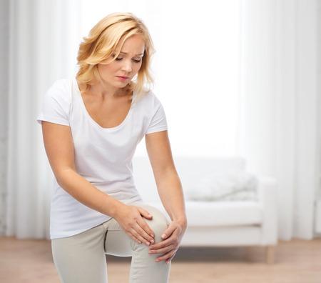人々 のヘルスケアそして問題のコンセプト - リビング ルームの背景の上足の痛みから苦しんでいる不幸な女性