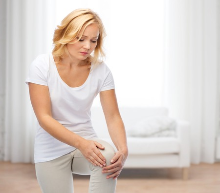 human joint: people, healthcare and problem concept - unhappy woman suffering from pain in leg over living room background