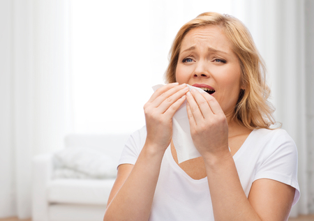 people, healthcare, rhinitis, cold and allergy concept - unhappy woman with paper napkin sneezing over living room background