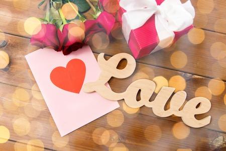 miłość, romans, Walentynki i święta pojęcie - zamknąć pudełko, czerwonych róż i kartkę z życzeniami z serca na drewnie