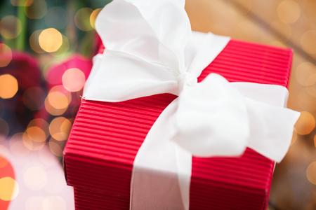 attentions: love, romance, valentines day and holidays concept - close up of red gift box with white bow