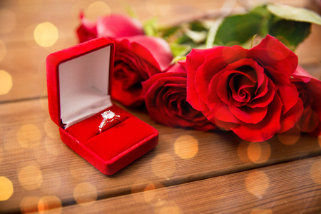 attentions: love, proposal, valentines day and holidays concept - close up of gift box with diamond engagement ring and red roses on wood