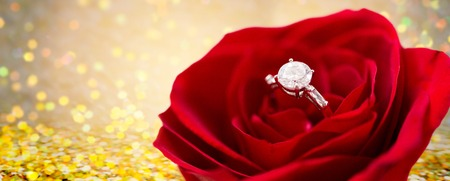 diamond ring: jewelry, romance, proposal, valentines day and holidays concept - close up of diamond engagement ring in red rose flower Stock Photo